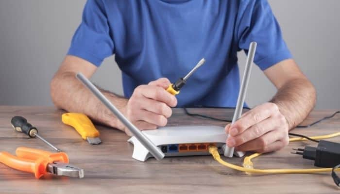 man fixing wifi router with screwdriver